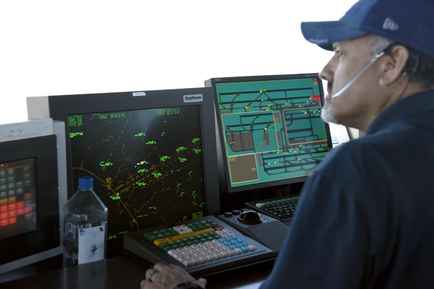 An air traffic controller talks with pilots inside the control tower at Los Angeles International Airport (LAX) in  Los Angeles, California
